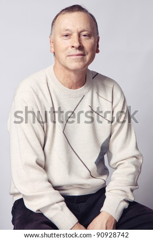 Portrait of an aged man over grey background - stock photo