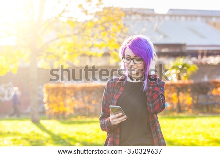 Portrait of an alternative style girl typing on smart phone. She has purple hair, eyeglasses and a squared shirt. Concepts of modern lifesrtyle and technology. - stock photo