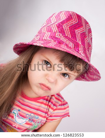 Portrait of an angry baby girl in hat. - stock photo