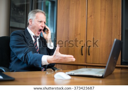 Portrait of an angry businessman yelling at phone - stock photo