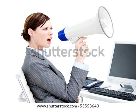 Portrait of an angry businesswoman using a megaphone in the office - stock photo