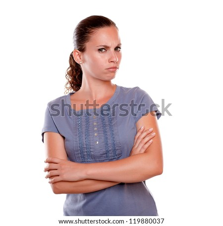 Portrait of an angry pensive latin young woman looking at you on blue blouse standing over white background - stock photo