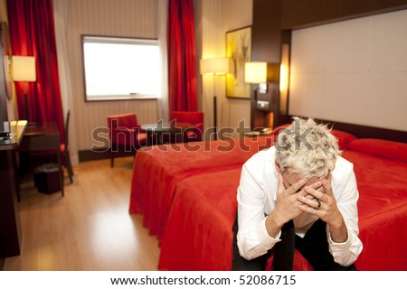 Portrait of an angry young business man sitting on a bed. - stock photo