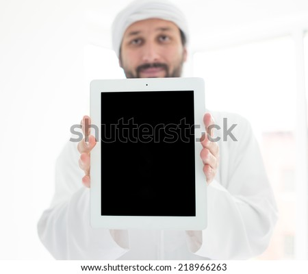 Portrait of an Arabian man with tablet and copy space - stock photo