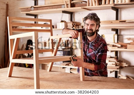 Portrait of an artisan designer, with new piece of furniture, finishing off the sanding of the chair in his studio, with shelves of wood behind him - stock photo