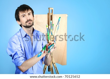 Portrait of an artist painting on easel. Shot in a studio. - stock photo