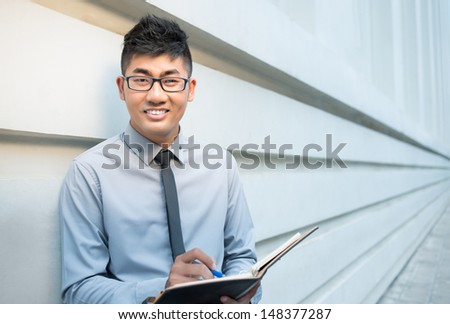 Portrait of an Asian businessman with a notepad looking at camera  - stock photo