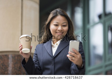 Portrait of an Asian businesswoman standing outside using her smart phone. - stock photo