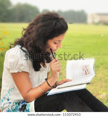 Portrait of an Asian / Indian college student thinking while reading a book at campus. - stock photo