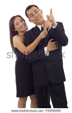 Portrait of an Asian man pointing at something interesting to his wife, girlfriend isolated over white background - stock photo