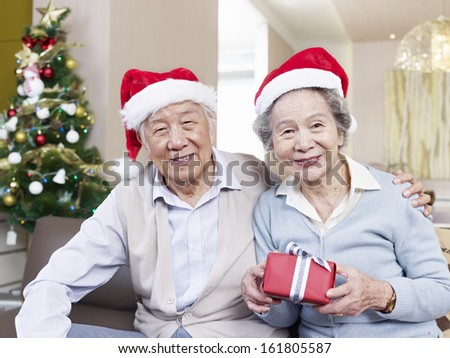 Portrait of an Asian senior couple with Christmas hats and gifts. - stock photo