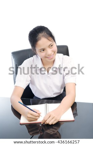 portrait of an Asian student write a book on white background - stock photo