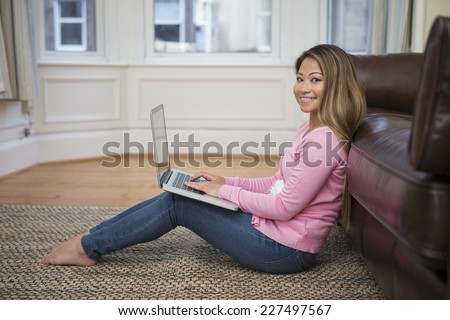 Portrait of an Asian woman sitting on floor, using laptop, in her living room at home.  Looking at camera  - stock photo