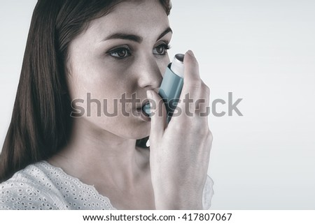 Portrait of an asthmatic woman against blue background - stock photo