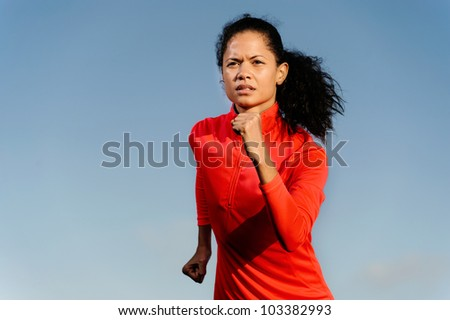 Portrait of an athlete running fitness woman with blue sky copyspace and red jacket. healthy athlete lifestyle. - stock photo