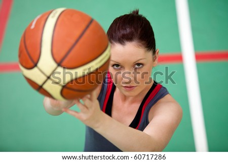 Portrait of an athletic young woman playing basket-ball in a gymnasium - stock photo