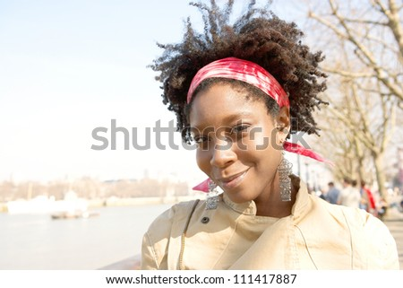 Portrait of an attractive african american woman sightseeing in London's river Thames while on vacation, smiling. - stock photo