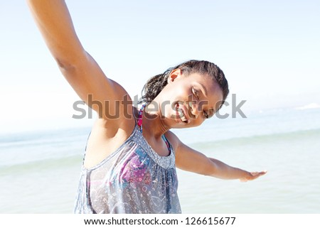 "Portrait of an attractive ""african american"" woman standing by the sea and smiling with her arms outstretched while on a beach vacation. - stock photo"