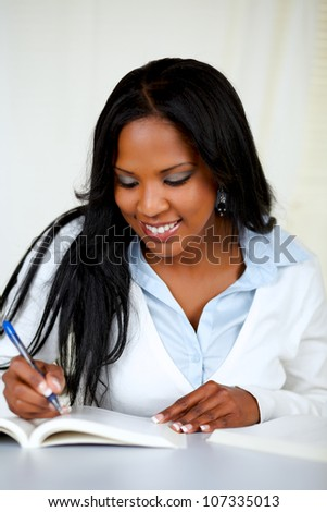 Portrait of an attractive african woman studying at soft colors composition - stock photo