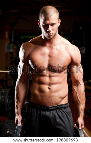 Portrait of an attractive athletic young man in a gym. - stock photo