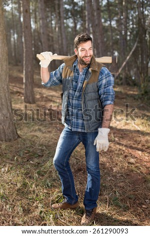 Portrait of an attractive bearded lumberjack guy posing in the forest with an axe on his shoulder - stock photo
