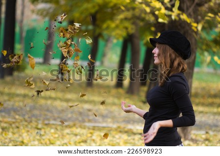 Portrait of an attractive beautiful pretty cute young caucasian cheerful smiling successful woman (girl, female, person) dressed in a black peak cap playing with old dry autumn foliage in a park.  - stock photo