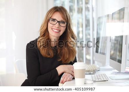 Portrait of an attractive businesswoman sitting at her desk in an office and drinking coffee while working on new investment project.  - stock photo