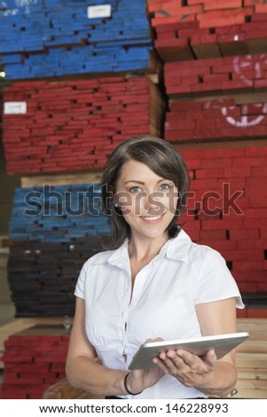 Portrait of an attractive businesswoman using tablet PC with stacked wooden planks in background - stock photo