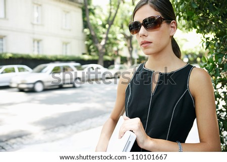 Portrait of an attractive businesswoman walking through a tree lined street in the financial district of a classic city. - stock photo