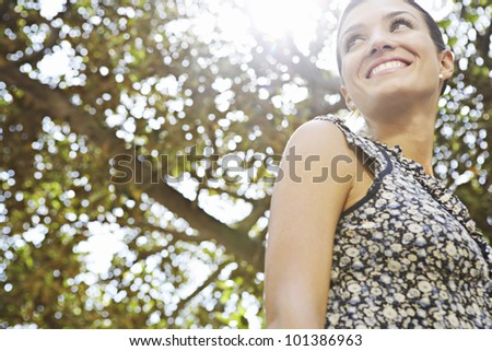 Portrait of an attractive businesswoman with foliage around her and sunlight coming through. - stock photo