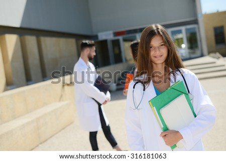 portrait of an attractive cheerful young medical student woman outdoor in front of hospital university campus - stock photo