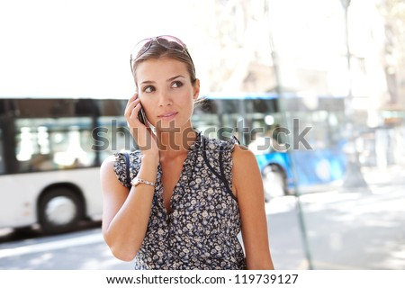 Portrait of an attractive commuting businesswoman using her smart phone in the city near a bus stop. - stock photo