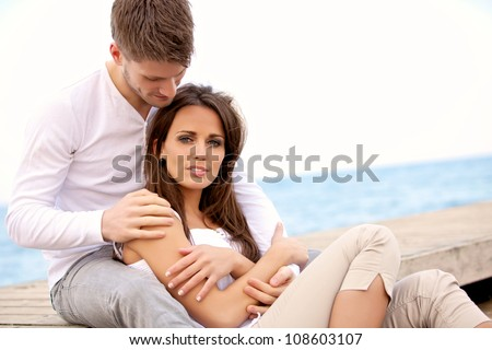 Portrait of an attractive couple sitting together on a pier - stock photo