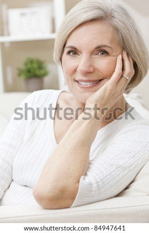 Portrait of an attractive elegant senior woman relaxing at home happy and smiling. - stock photo