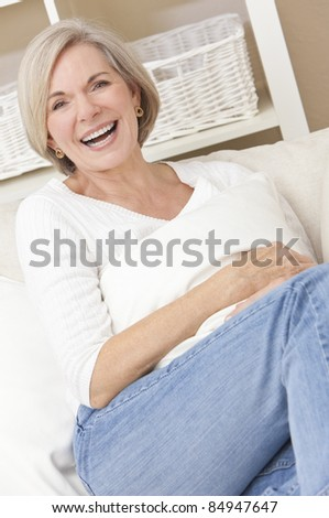 Portrait of an attractive elegant senior woman relaxing at home wearing jeans and laughing on the sofa - stock photo