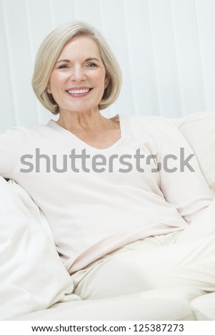 Portrait of an attractive elegant senior woman sitting relaxing at home. - stock photo