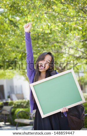 Portrait of An Attractive Excited Mixed Race Female Student Holding Blank Chalkboard and Carrying Backpack on School Campus. - stock photo