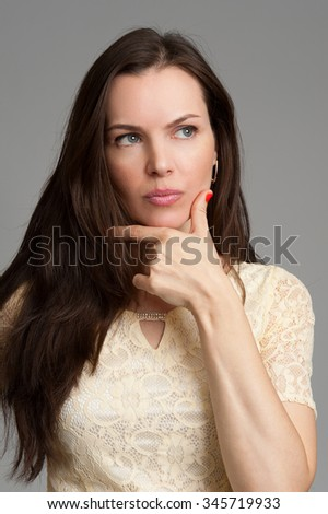 Portrait of an attractive fashionable young brunette woman thinking - stock photo