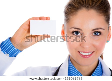 Portrait of an attractive female doctor standing against white background. and holding a business card  - stock photo