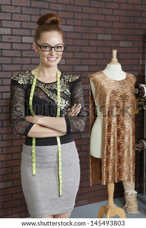 Portrait of an attractive female fashion designer standing arms crossed - stock photo