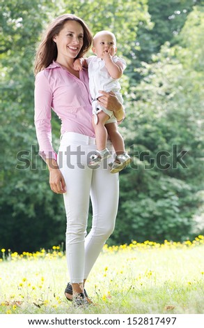 Portrait of an attractive female smiling and holding baby in the park - stock photo