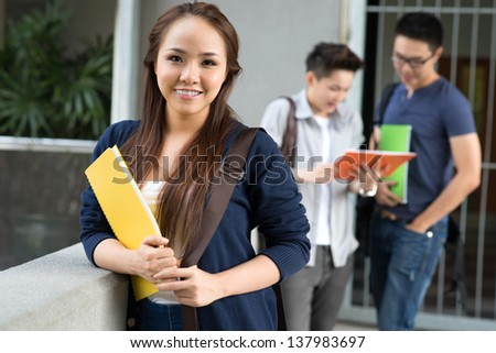 Portrait of an attractive female student on the foreground - stock photo