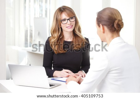 Portrait of an attractive financial officer businesswoman sitting in front of laptop and consulting with professional investment advisor. - stock photo