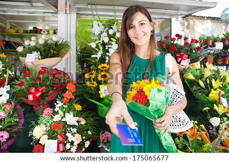 Portrait of an attractive florist store customer client woman buying a bouquet of fresh flowers and handing her credit card for payment in a flower market stall store. Outdoors business shopping. - stock photo