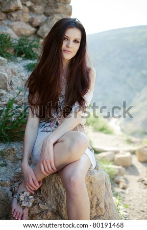 Portrait of an attractive girl with beautiful long hair sitting on rock - stock photo
