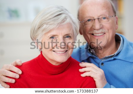 Portrait of an attractive happy senior couple posing close together looking at the camera with friendly warm smiles - stock photo