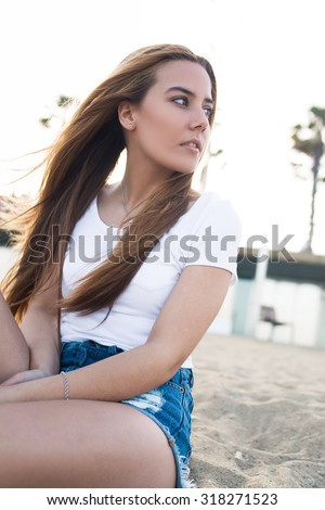Portrait of an attractive hipster girl sitting on the beach and focused looks aside while waiting for someone, charming woman relaxing after promenade in beautiful summer day during weekend - stock photo