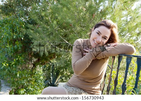 Portrait of an attractive hispanic middle aged mature woman in a home garden relaxing and leaning on an iron balcony banister, looking at camera and smiling with space, outdoors. - stock photo