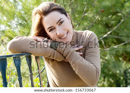 Portrait of an attractive hispanic middle aged mature woman in a home garden relaxing and leaning on an iron balcony banister, looking at camera and smiling, close up. - stock photo