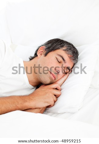 Portrait of an attractive man sleeping in his bed - stock photo